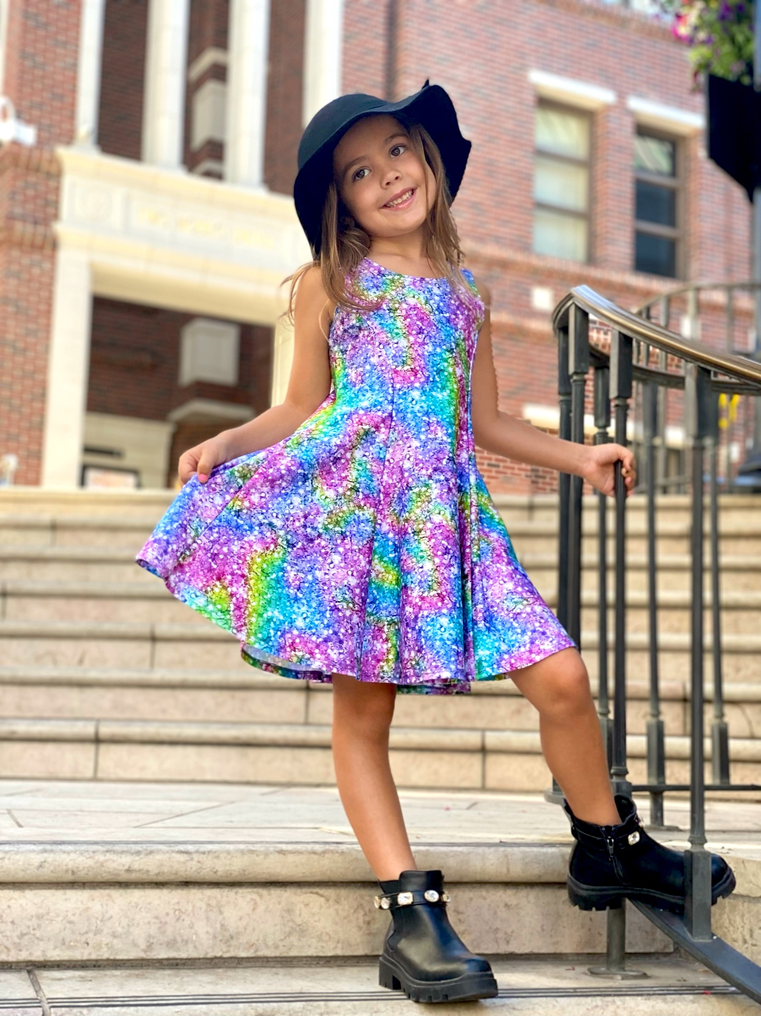 Young woman wearing a bright multicolored dress and standing on a flight of outdoor stairs.