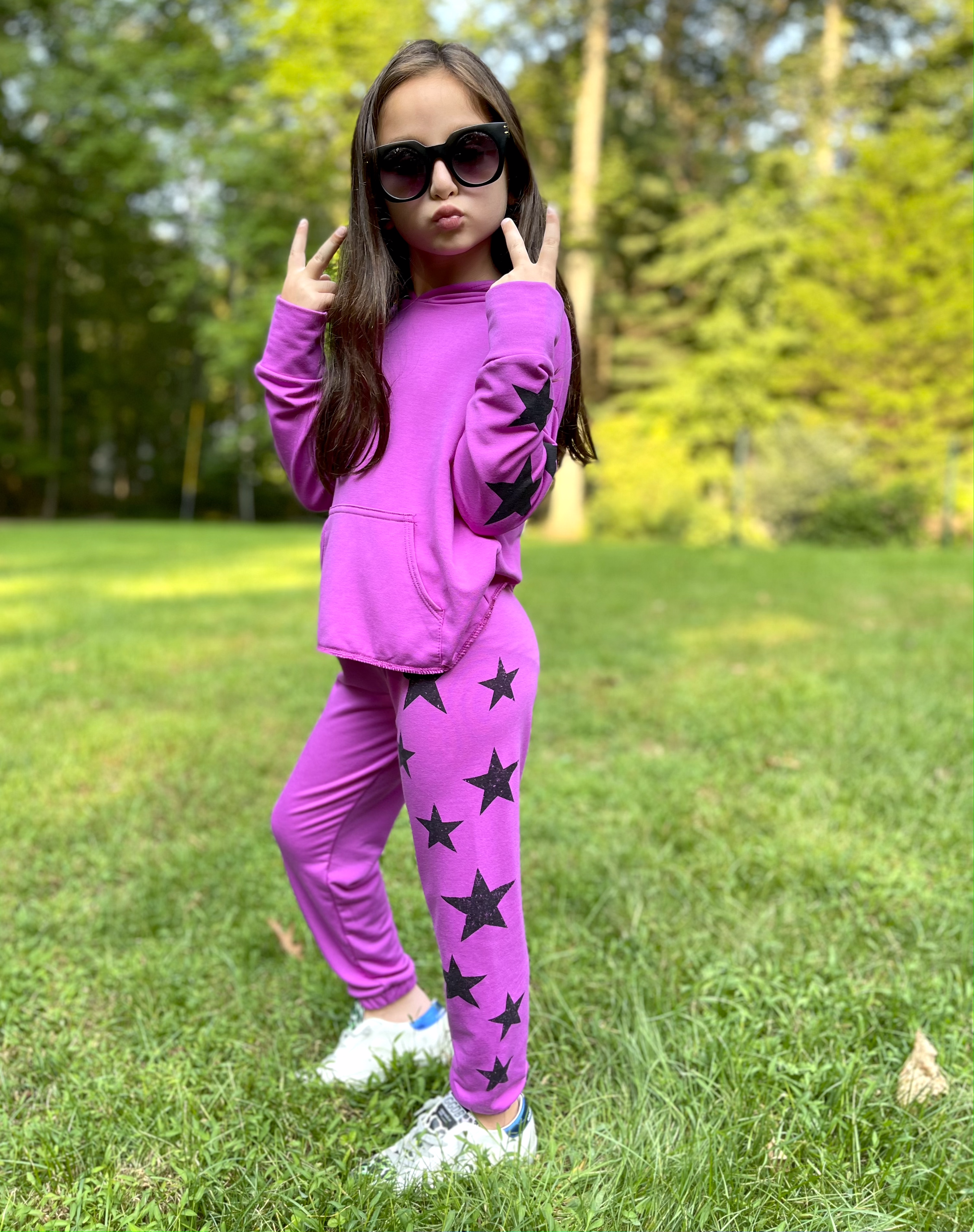 Young girl wearing purple star patterned shirt and pants.